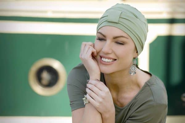 Woman with hair loss wearing a bamboo green hat.