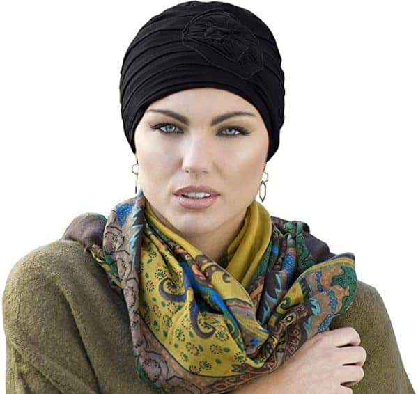 Woman with no hair wearing a black chemo hat.