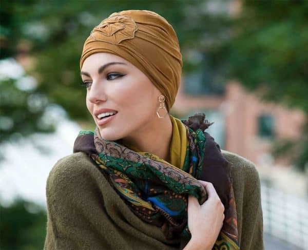 Woman with hair loss wearing a Primrose Silkline Turban in camel colour.