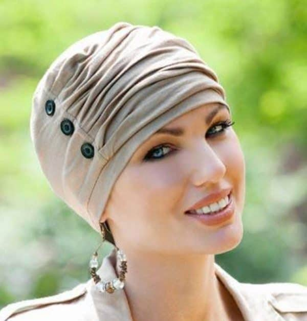 Woman with hair loss wearing a light brown Louise Turban with button detail.