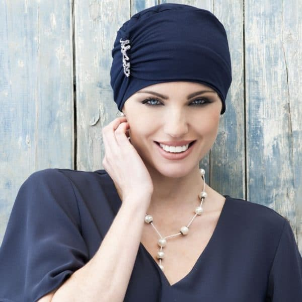 Woman with hair loss wearing a navy Soft Bamboo Iris Hat with a frill in the front.