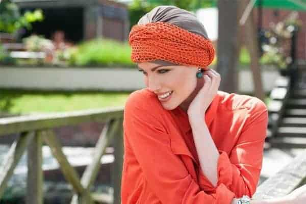 Woman with no hair wearing a taupe soft hat with an orange scarf.