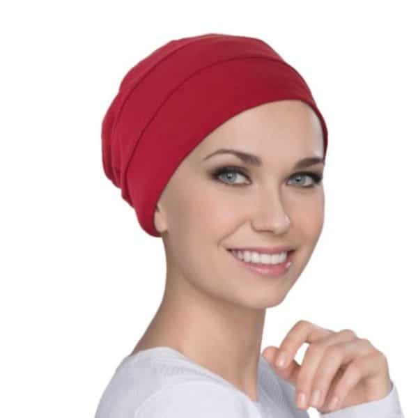 Woman with no hair wearing a red soft bamboo hat.
