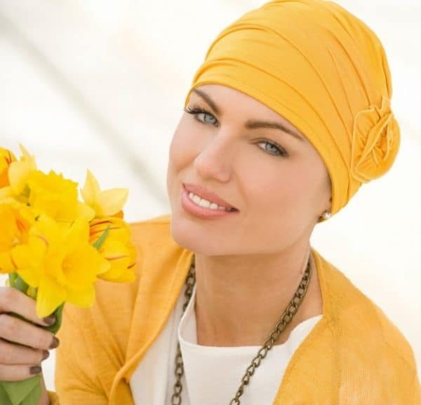 Woman with hair loss wearing a yellow chemo hat.