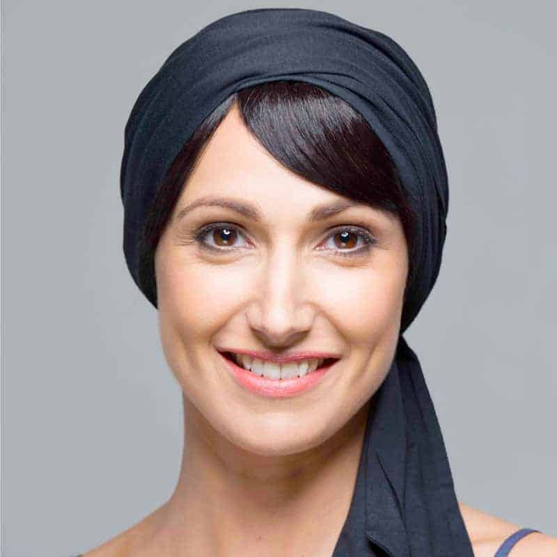 Woman with no hair wearing a Maia Fringe detachable underneath a hat.