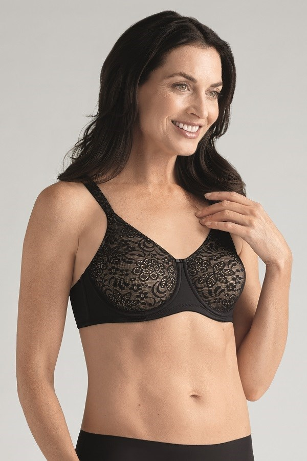 Woman post surgery wearing a mastectomy seam free bra in black and nude.