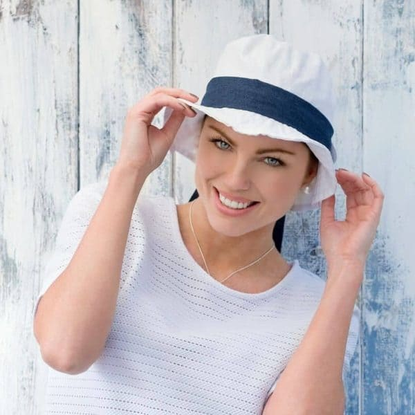 Woman with no hair wearing a white Lola Sun Hat with a navy scarf tied around the hat.