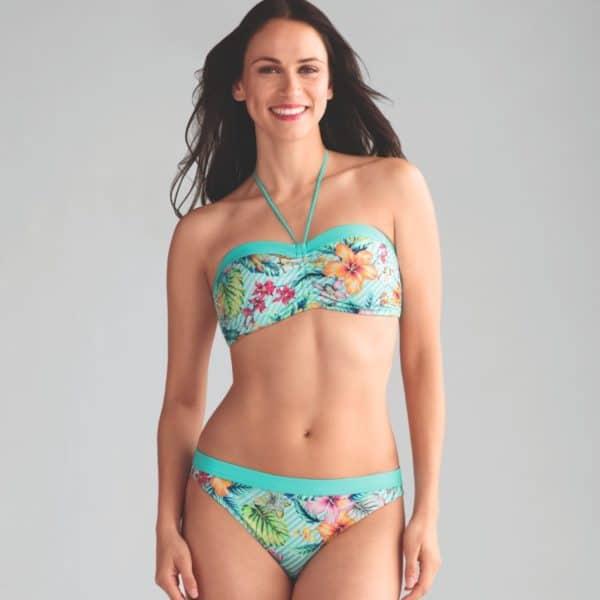 Woman post surgery wearing a mastectomy bikini in turquoise.