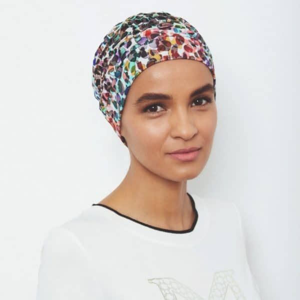 Woman with no hair wearing a patterned Florida Patterned Turban.