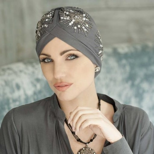 Woman with no hair wearing a soft bamboo turban in grey crafted with delicate beading.
