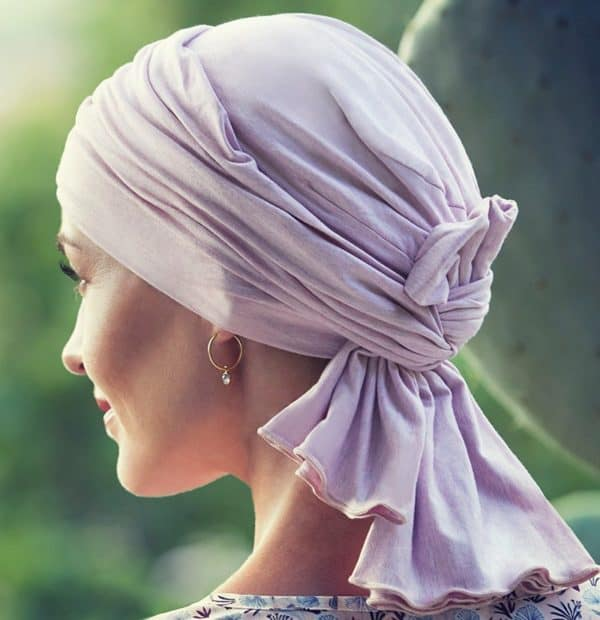 Woman with hair loss wearing light pink scarf made from soft bamboo with extra fabric to create volume.