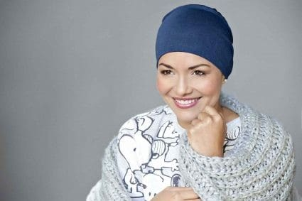 Woman with no hair wearing a soft bamboo sleep hat in navy.