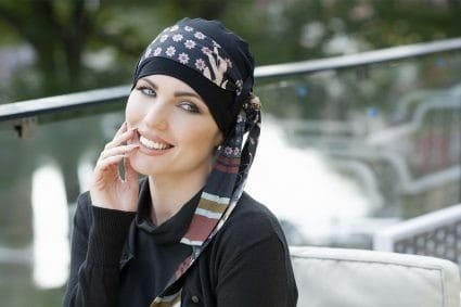 Woman with no hair wearing a black bamboo hat with a flower print scarf around it.