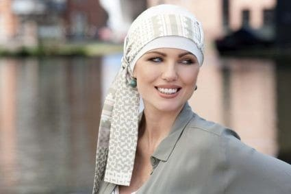 Woman with no hair wearing a white bamboo hat with a flower print scarf around it.