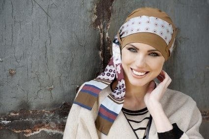 Woman with no hair wearing a bamboo hat with scarf.