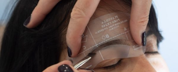 Woman using an eyebrow stencils to shape the eyebrow.