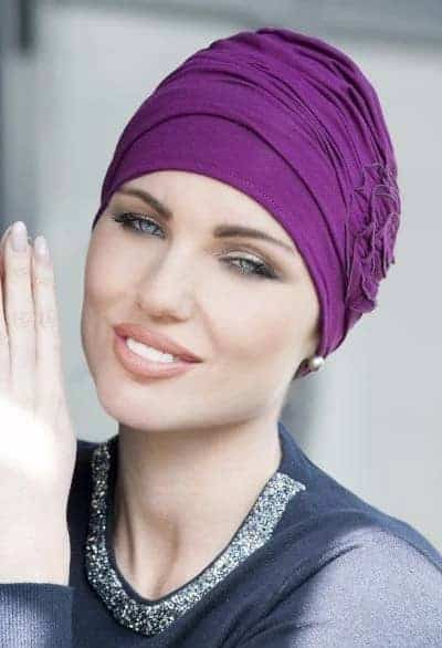 Women with no hair wearing chemo hat in purple